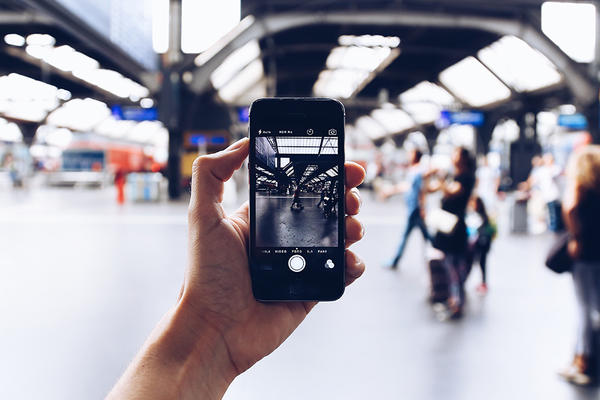 a hand holding a cell phone filming a blurred scene at an airport. Photo by Oleg Magni on Pexels.