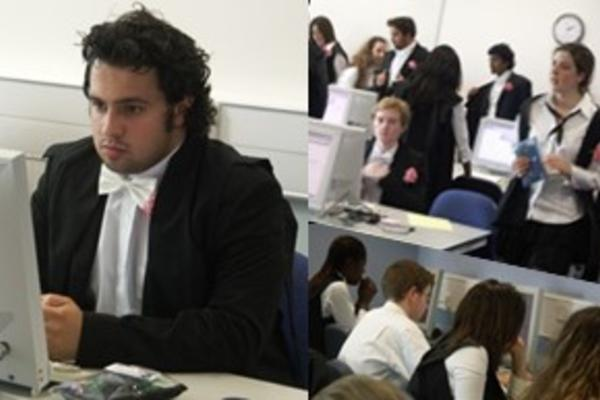 Oxford students in subfusc robes with carnations take exams online in a shared computer room. Photo by MSDLT (CC-BY-SA-NC).