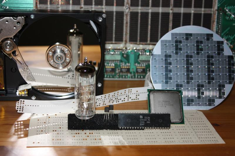 Images of some early computer parts. At the back: core memory (tiny tiny doughnuts of metal woven onto wires). At the front: A punched card