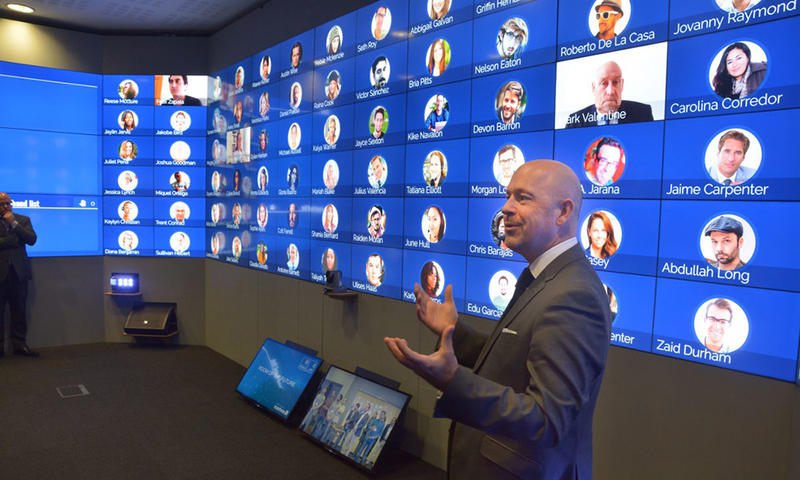 A man standing in a room covered with screens, the Oxford Hub for International Virtual Education (HIVE)