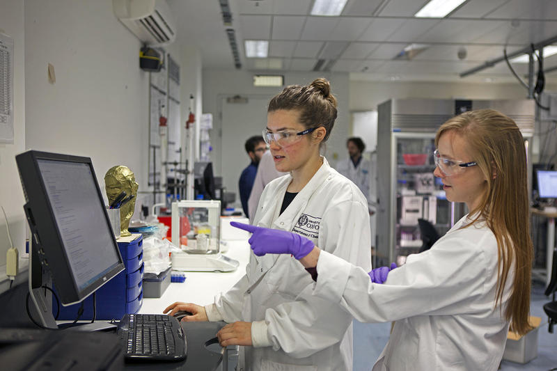 Two students looking and pointing at a computer screen inside a laboratory. Photo by Peter Hudston.